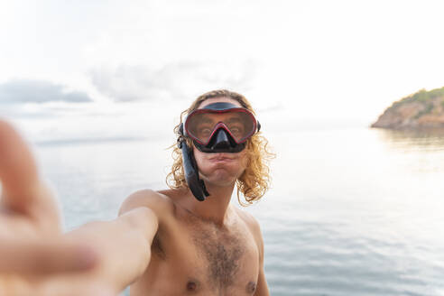 Young man with snorkel making a face on the beach - AFVF04982