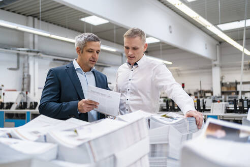 Two businessmen discussing paper in a factory - DIGF09133