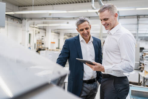 Two smiling businessmen looking at tablet in a factory - DIGF09172