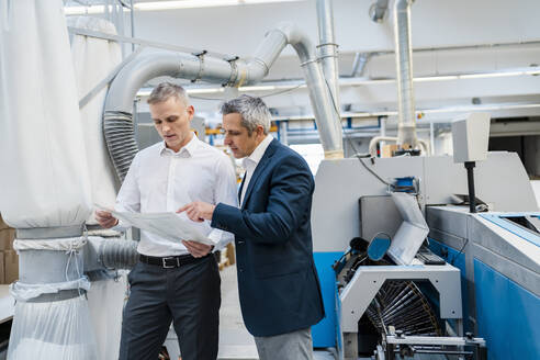 Two businessmen discussing paper in a factory - DIGF09181
