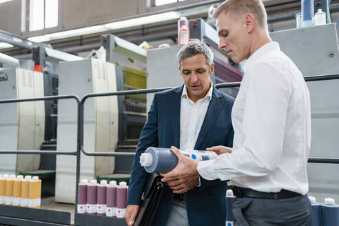 Two businessmen examining product in a factory - DIGF09196