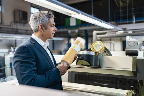 Businessman in a factory examining product - DIGF09202