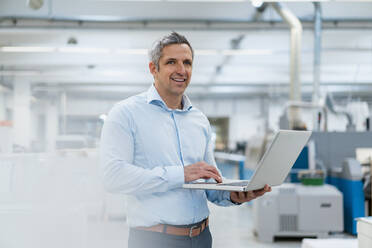 Smiling businessman using laptop in factory - DIGF09253