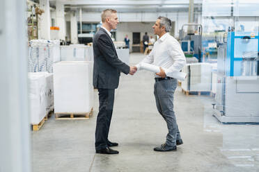 Two businessmen shaking hands in a factory - DIGF09259