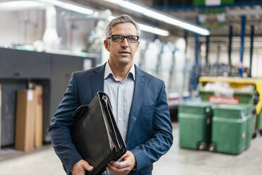 Portrait of a businessman with glasses and briefcase in a factory - DIGF09283