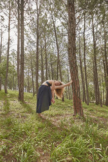 Barefoot young woman doing stretching exercise in the woods - VEGF01308
