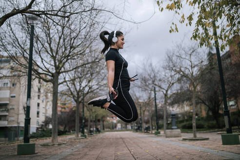 Young woman in black sportswear jumping in the air while listening music with headphones - GRCF00019