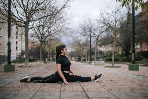 Young woman in black sportswear doing the splits on pavement - GRCF00022