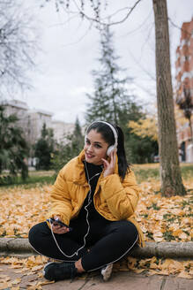 Portrait of smiling young woman  listening music with headphones and smartphone in autumn - GRCF00025