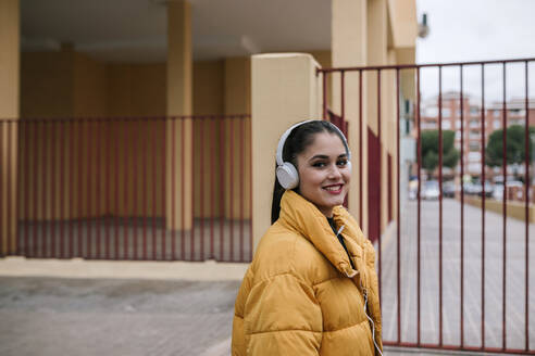 Portrait of happy young woman listening music with headphones outdoors - GRCF00028