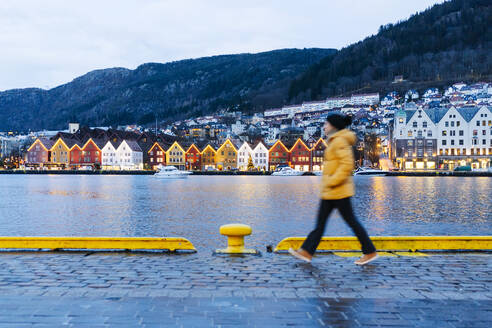 Woman wearing a yellow jacket and walking at harbour in Bergen, Norway - DGOF00005