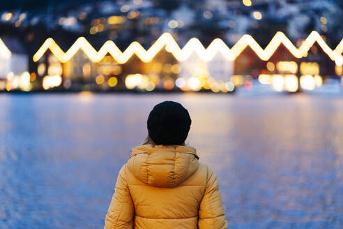 Rear view of woman wearing a yellow jacket and standing at harbour in Bergen, Norway - DGOF00008