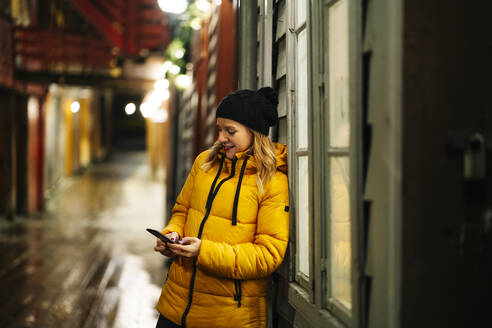 Woman wearing a yellow jacket and using smartphone in Bergen, Norway - DGOF00011