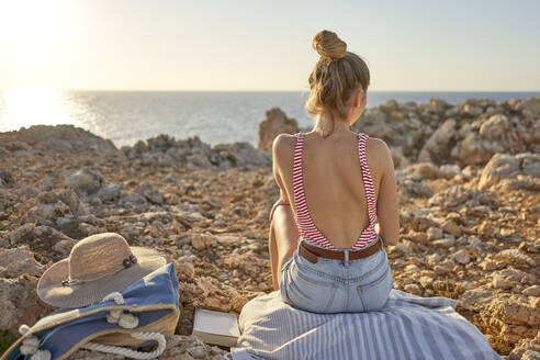 Young woman sitting on rocky beach, relaxing, Menorca, Spain - EPF00643
