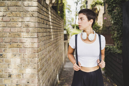 Portrait of woman with headphones and backpack - FBAF01253