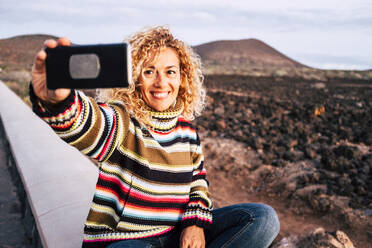 Portrait of woman wearing colorful pullover and taking a selfie, Tenerife, Spain - SIPF02102
