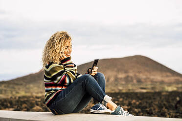 Portrait of woman wearing colorful pullover and using smartphone, Tenerife, Spain - SIPF02105