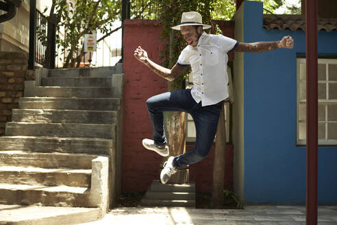 Portrait of young man with vitiligo wearing a hat, jumping in the street - VEGF01338