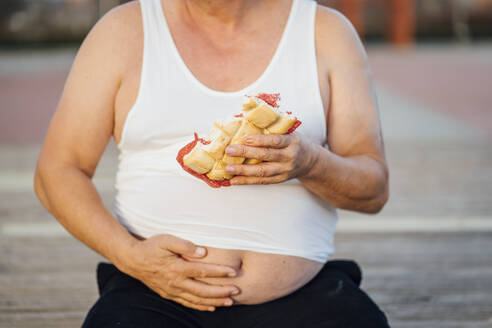 Man with beer belly holding sandwich - OCMF00989