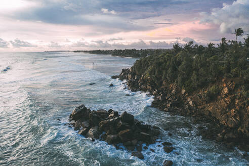 SriLanka, Southern Province, Ahangama, Aerial view of rocky shore of Indian Ocean at dusk - DAWF01114