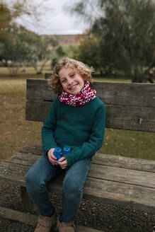 Portrait of happy boy with binoculars sitting on bench in autumn - GRCF00034