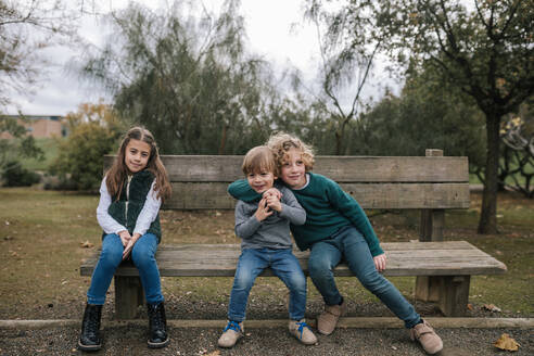 Group picture of three children sitting on wooden bench outdoors - GRCF00037