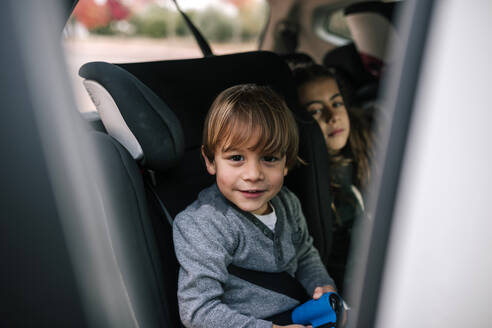 Portrait of smiling little boy sitting in child's seat in car - GRCF00046