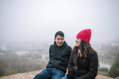 Young Mexican couple interacting on a foggy day - GRCF00051
