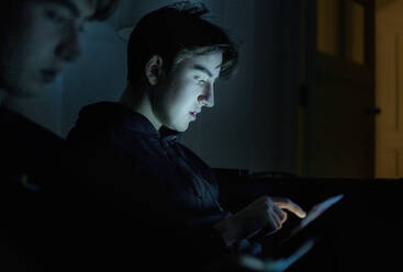 Two teenage boys using technology at home in the dark - AJOF00084
