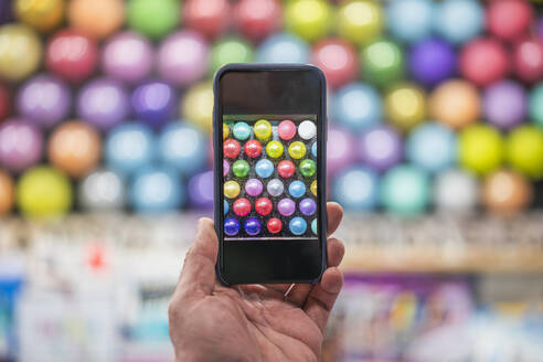 Hnad holding smartphone taking picture of balloons at fairground booth - DLTSF00393