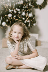 Portrait of blond little girl sitting in front of Christmas tree - EYAF00803