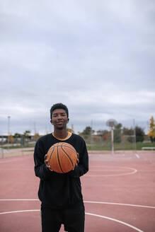 Teenager holding basketball - GRCF00053