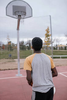 Rear view of teenager playing basketball - GRCF00065