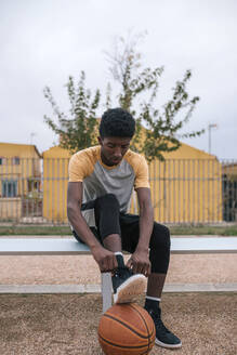 Teenager with basketball, tying shoes - GRCF00071