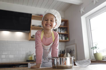 Portrait of smiling girl wearing chef's hat in the kitchen - KMKF01164