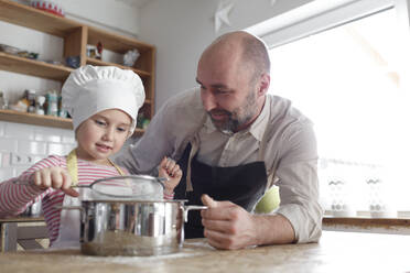 Father and daughter cooking in the kitchen - KMKF01167