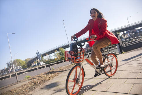 Young woman riding through the city on a rental bike - AJOF00095