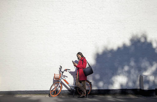 Young woman using rental bike with smartphone app l - AJOF00101
