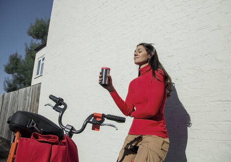 Young woman with bicycle, leaning on wall, drinking coffee from reusable cup - AJOF00104