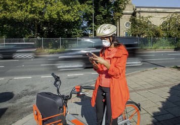 Young woman with helmet and face mask, sitting on bicycle, using smartphone - AJOF00113