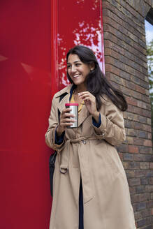 Young businesswoman with reusable coffee cup, leaning on wall - AJOF00119