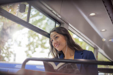 Young woman listening music on a bus with earphones, looking out of window - AJOF00122