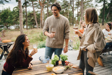 Smiling friends enjoying drinks while talking during garden party in yard - MASF16145