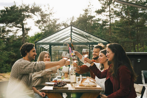 Male and female friends toasting wineglasses while enjoying dinner at garden party - MASF16151