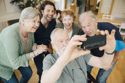 Disabled senior man taking selfie with friends and male nurse at retirement home - MASF16208