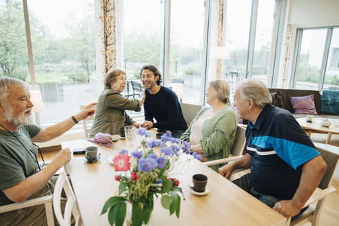 Smiling man sitting amidst senior people sitting at dining table against window in nursing home - MASF16241