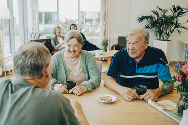 Elderly senior friends talking while sitting at dining table in nursing home - MASF16247