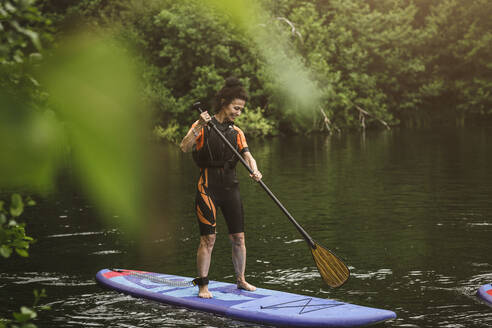 Full length of smiling senior woman paddleboarding in sea during SUP course - MASF16280