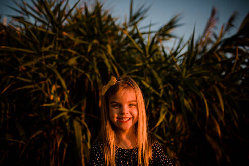 Young Girl Smiling at Camera During Sunset - CAVF72756