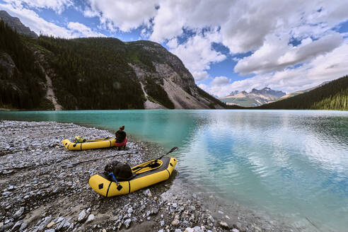 A couple pulls up onto a glacial bar in their rafts on Cirque Lake - CAVF72774